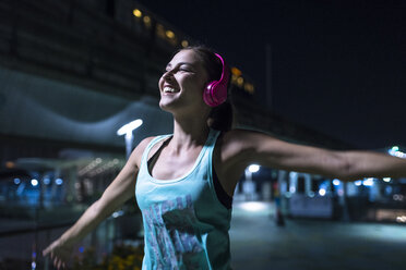 Happy young woman with pink headphones listening to music in modern urban setting at night - SBOF01026