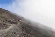 Reunion, Reunion National Park, Shield volcano Piton de la Fournaise, female tourist hiking to crater - FOF09652