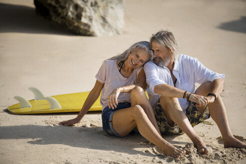 Affectionate senior couple with surfboard lying on beach - SBOF01034