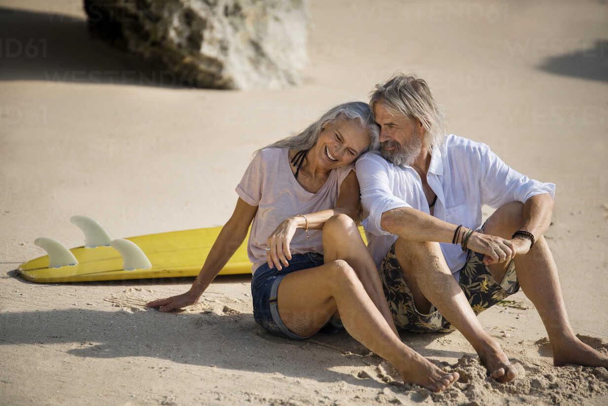 Affectionate senior couple with surfboard lying on beach - SBOF01034 - Steve Brookland/Westend61