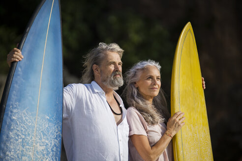 Affectionate senior couple with surfboards at beach - SBOF01040