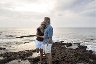 Affectionate senior couple embracing at the sea - SBOF01049