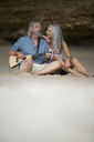 Handsome senior couple sitting on the beach, man playing guitar - SBOF01055