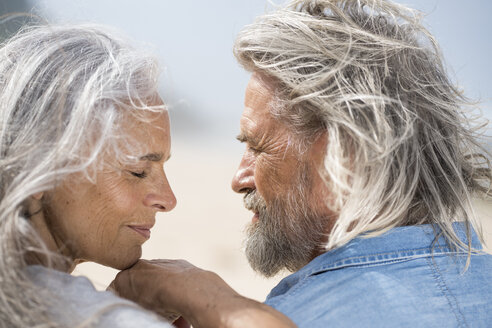Affectionate senior couple looking into each others eyes in front of the sea - SBOF01067