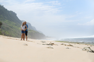 Affectionate senior couple standing on the beach - SBOF01070