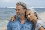 Handsome senior couple embracing at the beach - SBOF01076