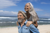 Handsome senior couple having fun at the beach - SBOF01079
