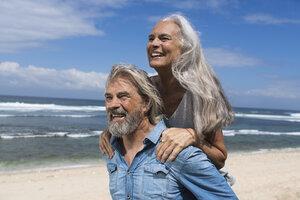 Handsome senior couple having fun at the beach - SBOF01079