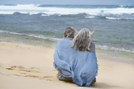 Senior couple sitting on the beach, wrapped in a blanket - SBOF01082