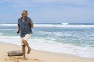 Handsome senior man with headphones dancing on the beach - SBOF01091