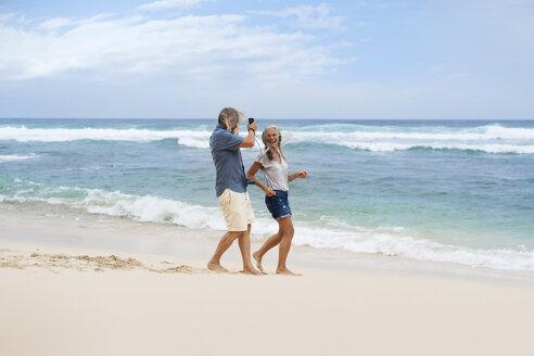 Handsome senior couple with headphones dancing on the beach - SBOF01094