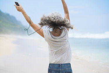 Senior woman with headphones dancing on the beach - SBOF01097