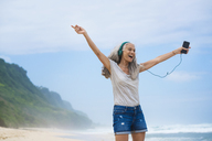 Senior woman with headphones dancing on the beach - SBOF01100