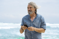Handsome senior man with smartphone on the beach - SBOF01106