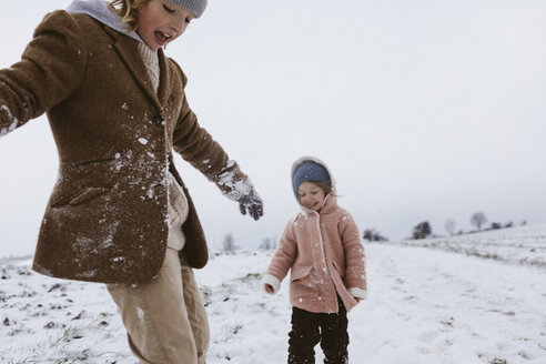 Brother and little sister playing together on snow-covered meadow - KMKF00126