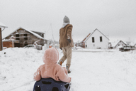 Boy pulling sledge with little sister in snow - KMKF00129