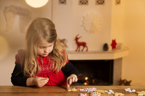 Little girl garnishing Christmas cookies with hundreds and thousands - NEKF00003