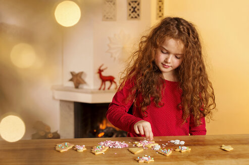 Little girl garnishing Christmas cookies with hundreds and thousands - NEKF00006
