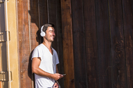 Happy young man with cell phone and headphones leaning against wooden wall - SIPF01915