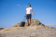 Man standing with rolling suitcase at the beach - SIPF01927