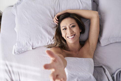 Portrait of smiling woman lying in bed giving a hand - IGGF00352
