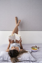 Relaxed woman reading a book in bed - IGGF00358