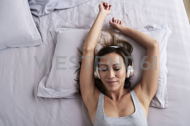 Relaxed woman listening to music in bed - IGGF00361