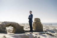 Businessman figurine standing on sand by sand buildings - FLAF00005