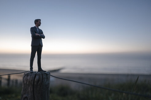 Businessman figurine standing on a fence at the beach, looking at the sea - FLAF00011