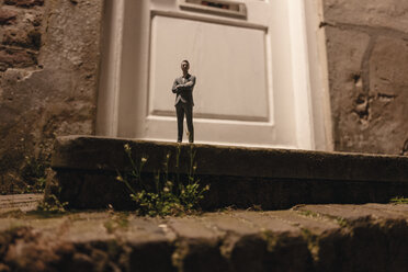 Businessman figurine standing on stairs in front of an entrance door - FLAF00014
