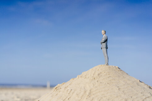 Businessman figurine standing on sand hill looking at view - FLAF00017