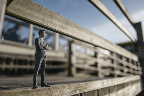 Businessman figurine standing on wooden stairs - FLAF00020