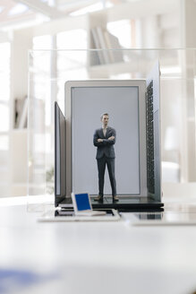 Businessman figurine standing on portable devices in a glass cage - FLAF00026
