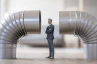 Businessman figurine standing between two stove pipes - FLAF00035