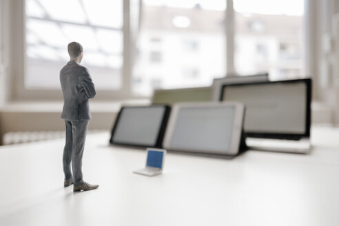 Businessman figurine standing on desk, facing mobile devices - FLAF00038