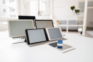 Miniature laptop and mobile devices on a desk - FLAF00044