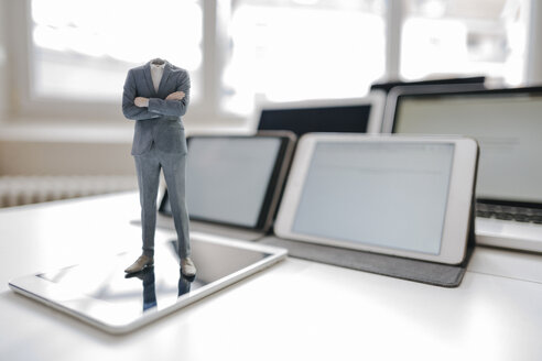 Headless businessman figurine standing on digital tablet on a desk - FLAF00047