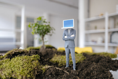 Businessman figurine with laptop head standing on green moss - FLAF00053