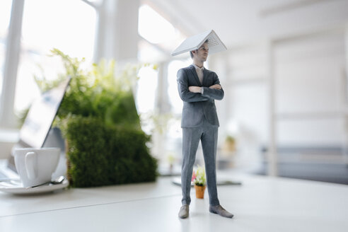 Businessman figurine standing on desk, balancing a laptop on top of his head - FLAF00059