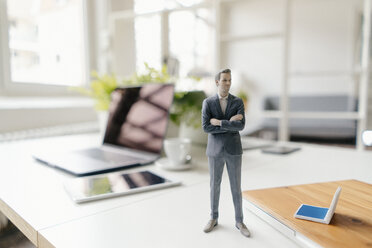Businessman figurine standing on a desk with mobile devices - FLAF00062