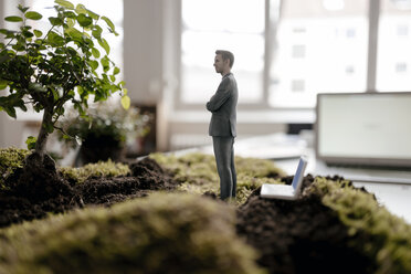 Businessman figurine with laptop standing on green moss - FLAF00065