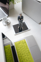 Businessman figurine standing on a desk with mobile devices and a cup of coffee - FLAF00068