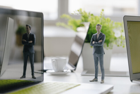 Businessman figurine standing on desk with mobile devices - FLAF00071