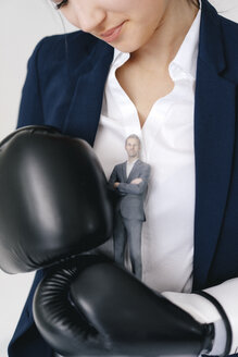 Businesswoman holding businessman figurine between boxing gloves - FLAF00074