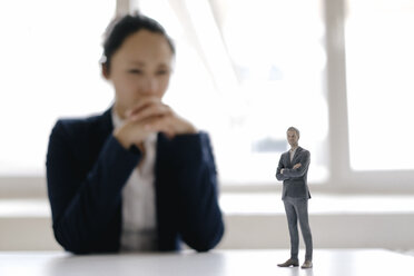 Businesswoman watching businessman figurine, standing on her desk - FLAF00077