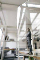 Businessman figurine standing in modern office, looking through glass pane - FLAF00080