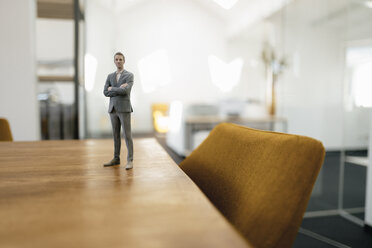 Businessman figurine standing on desk in modern office - FLAF00083