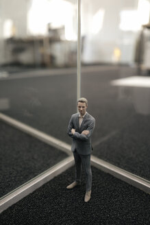 Businessman figurine standing between glass panes - FLAF00086