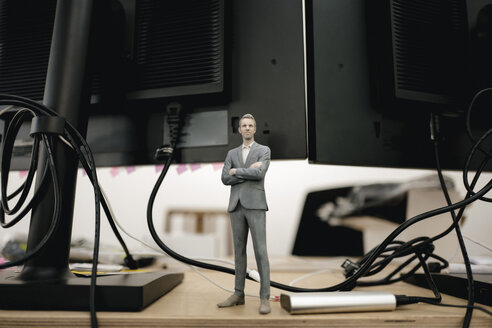Businessman figurine standing under computer screens - FLAF00089