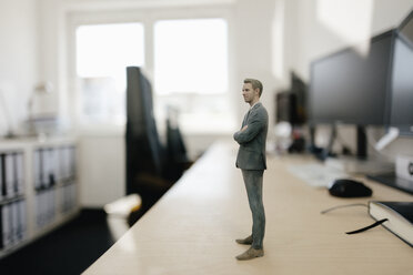 Businessman figurine standing on desk in modern office - FLAF00095